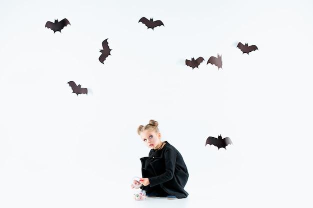 Kleine meisje heks in zwarte lange jurk en magische accessoires. halloween. Gratis Foto
