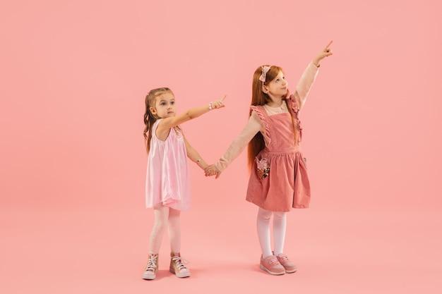 Kleine meisjes die op roze muur wijzen Gratis Foto