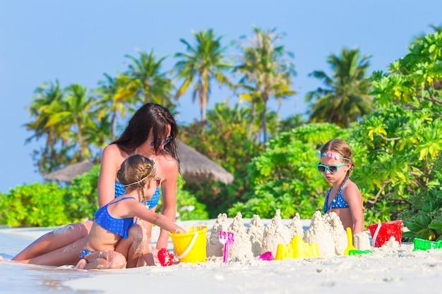 Kleine meisjes en gelukkige moeder spelen met strand speelgoed op zomervakantie Premium Foto