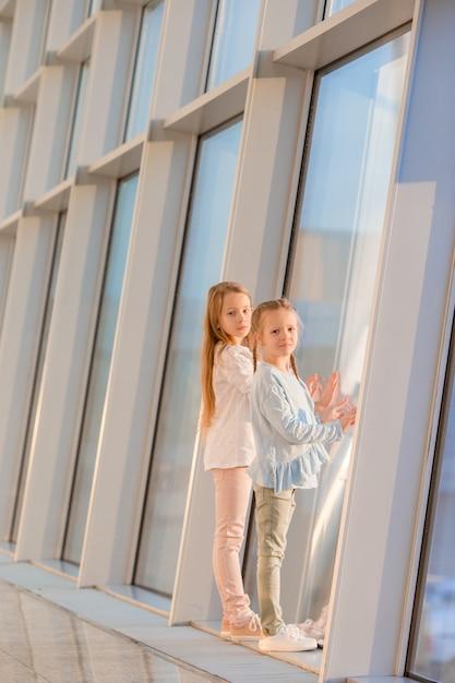 Kleine meisjes in de luchthaven in de buurt van groot raam tijdens het wachten op instappen Premium Foto