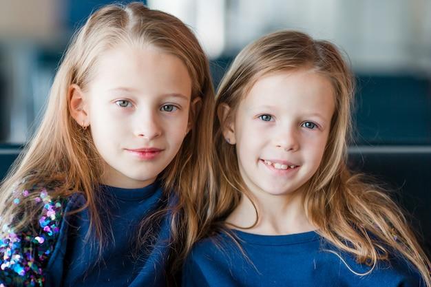 Kleine meisjes in luchthaven terwijl wachten op instappen Premium Foto