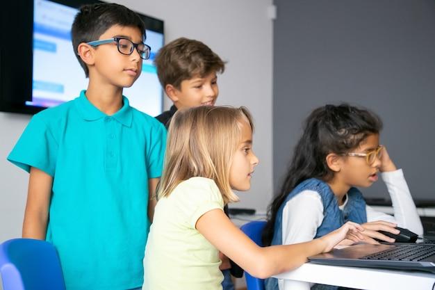 Kleine meisjes met behulp van laptops, studeren aan de computerschool en aan tafel zitten Gratis Foto