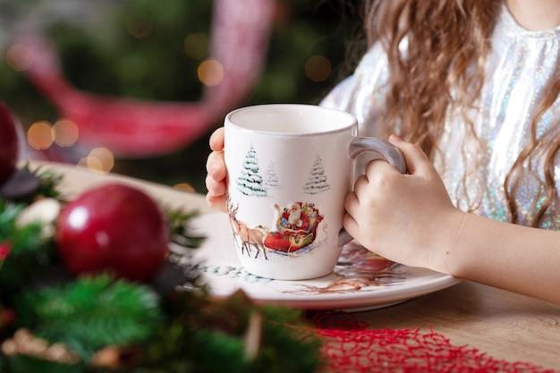 Kleine meisjeshanden die een kopje thee houden op de tafel staan Premium Foto