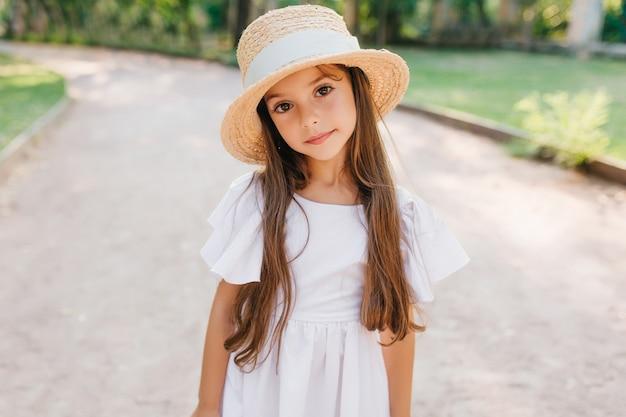 Kleine modieuze dame met lange wimpers die met interesse op zoek terwijl ze op de weg staat in een elegante hoed. outdoor portret van verlegen bruinharige meisje schattige witte jurk dragen. Gratis Foto