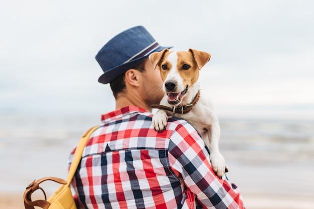 Kleine mooie hond op eigenaar` s handen. jonge man draagt zijn huisdier en tas, staan aan kust Premium Foto
