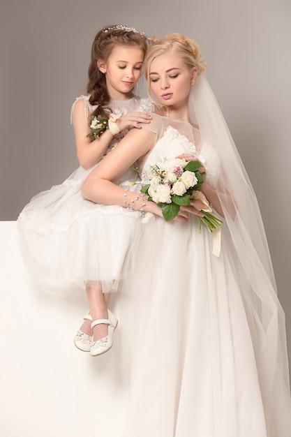 Kleine mooie meisjes met bloemen gekleed in trouwjurken Gratis Foto