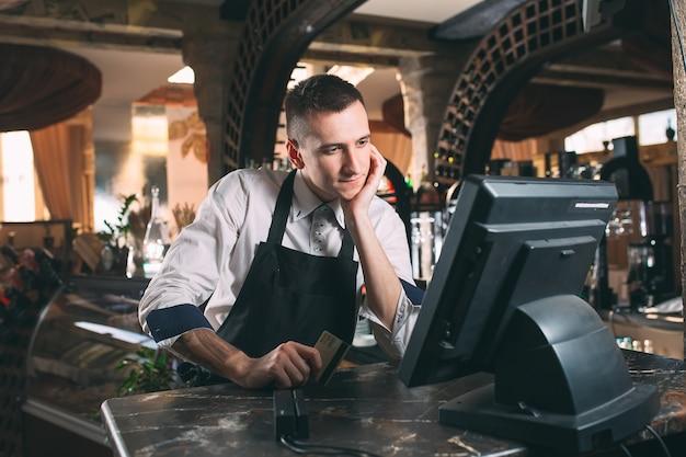 Kleine onderneming, mensen en de dienstconcept - gelukkige mens of kelner in schort bij teller met kassa werken bij bar of koffiewinkel Premium Foto