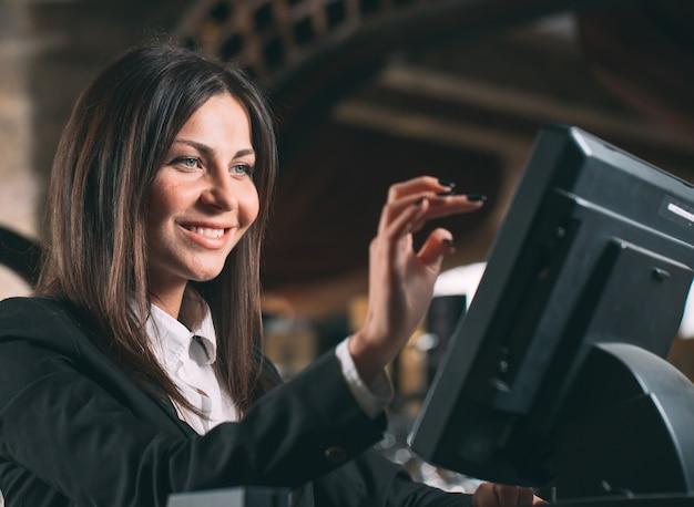 Kleine onderneming, mensen en de dienstconcept - gelukkige vrouw of kelner of manager in schort bij teller met kassa werken bij bar of koffiewinkel Premium Foto