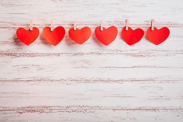 Kleine papieren harten vastgemaakt aan touw op de muur Gratis Foto