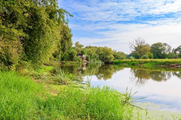 Kleine rivier op een achtergrond van groene bomen aan de oevers tegen blauwe hemel. rivierlandschap op zonnige herfstochtend Premium Foto