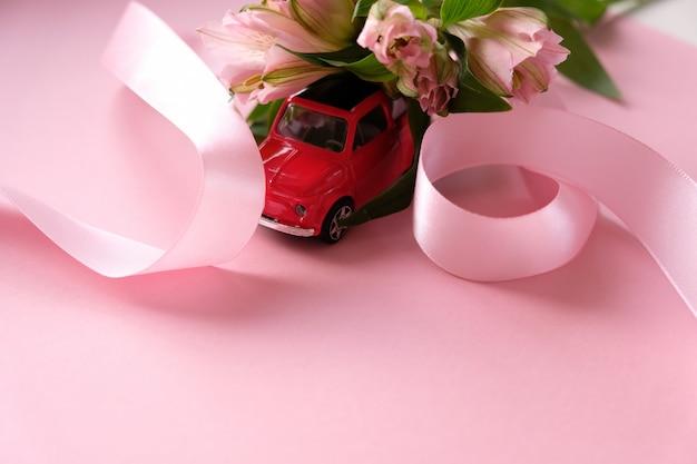 Kleine rode speelgoedauto draagt een boeket roze bloemen Premium Foto