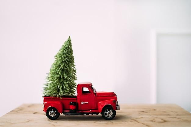 Kleine rode speelgoedauto met groene kerstboom op houten en witte achtergrond staan ?? in de buurt van de muur. Premium Foto