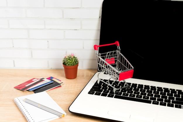 Kleine rode winkelwagentje of trolley op laptop toetsenbord. technologie bedrijfs online het winkelen concept Premium Foto