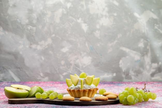 Kleine romige cake met gesneden fruit op gekleurd bureau, cake zoete suiker bak Gratis Foto