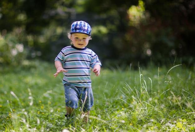 Kleine schattige baby loopt op het gras Premium Foto