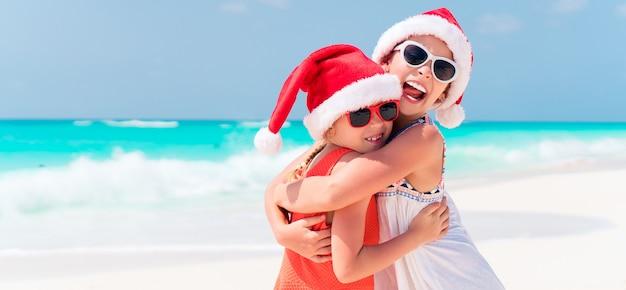 Kleine schattige meisjes in santa hoeden tijdens strandvakantie hebben plezier samen Premium Foto