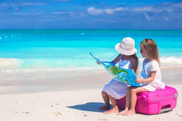 Kleine schattige meisjes met grote koffer en een kaart op tropisch strand Premium Foto