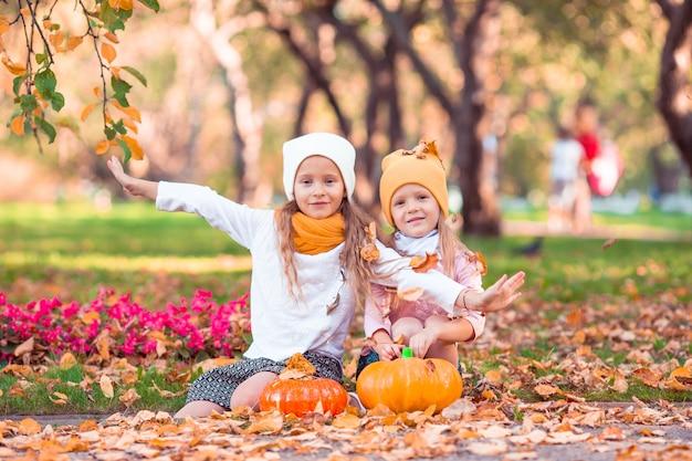 Kleine schattige meisjes met pompoen buitenshuis op een warme herfstdag. Premium Foto
