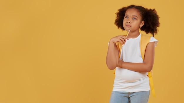 Kleine school meisje kopie ruimte gele achtergrond Gratis Foto