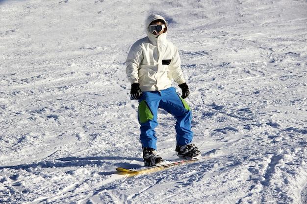 Kleine snowboarder op blauwe hemelachtergrond. Premium Foto