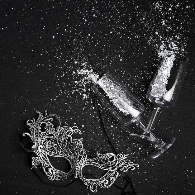 Kleine spangles verspreid uit glazen met masker Gratis Foto