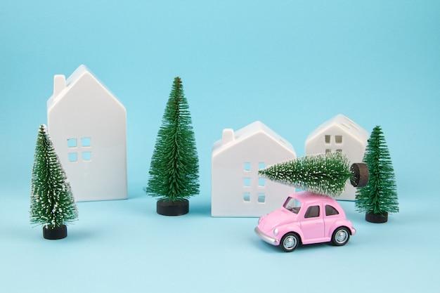 Kleine stuk speelgoed auto die kerstmisboom over het dak draagt. sesonal vakantie, wenskaart Premium Foto