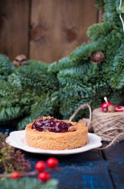 Kleine taart met veenbessen en jam en kerstboom Premium Foto