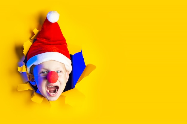 Kleine vrolijke kerstman in hoed glimlacht, weggaand uit de haveloze gele achtergrond verlicht door neonlicht Premium Foto