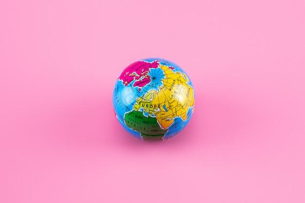 Kleine wereldbol bal op roze. Premium Foto