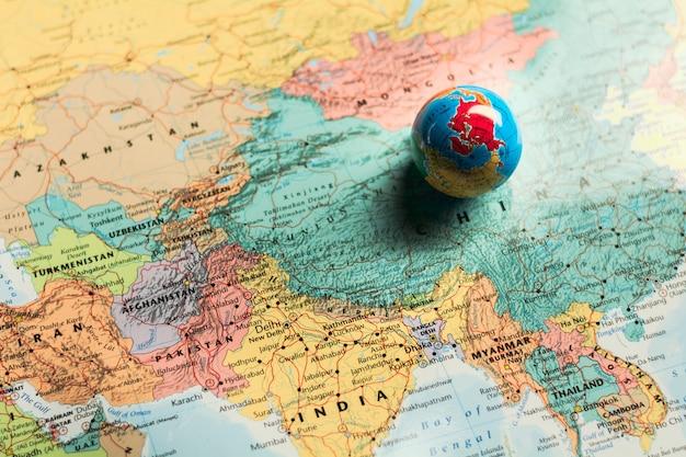 Kleine wereldbol bal op wereldkaart. - bedrijfs- en toekomstconcept. Premium Foto