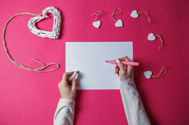 Kleine witte houten harten en groot wit rieten houten hart met kabel op roze achtergrond met exemplaarruimte. de dagkaart van heilige valentine met vrouwenhanden die met roze pen op wit blad van document schrijven. Premium Foto