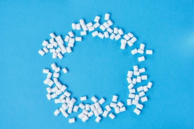 Kleine witte marshmallows verspreid over een blauwe achtergrond, cirkel van marshmallows bovenaanzicht Premium Foto