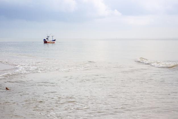 Kleine woden vissersboot liet het anker vallen bij de kustlijn. Premium Foto