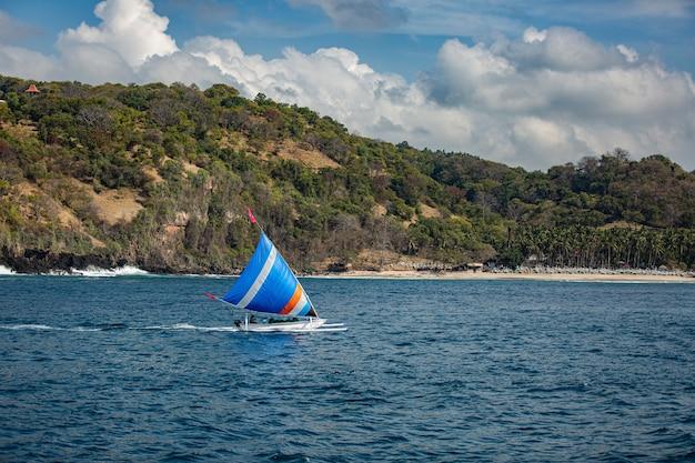 Kleine zeilboot drijft op water met geweldig uitzicht op de bergen. Gratis Foto