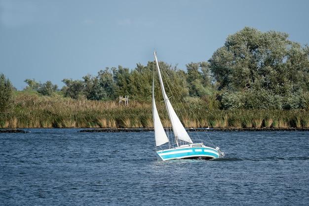 Kleine zeilboot op een meer omgeven door bomen in het zonlicht Gratis Foto