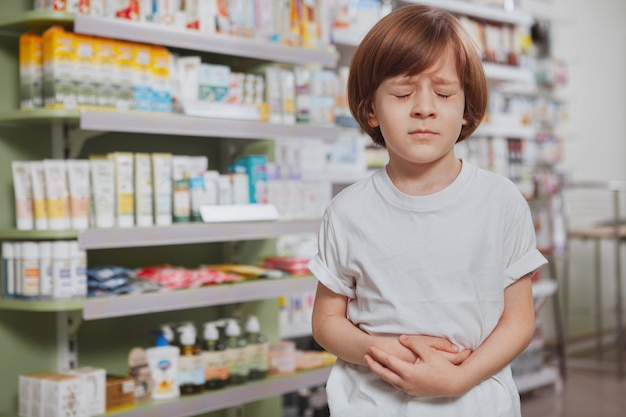 Kleine zieke jongen bij de apotheek Premium Foto