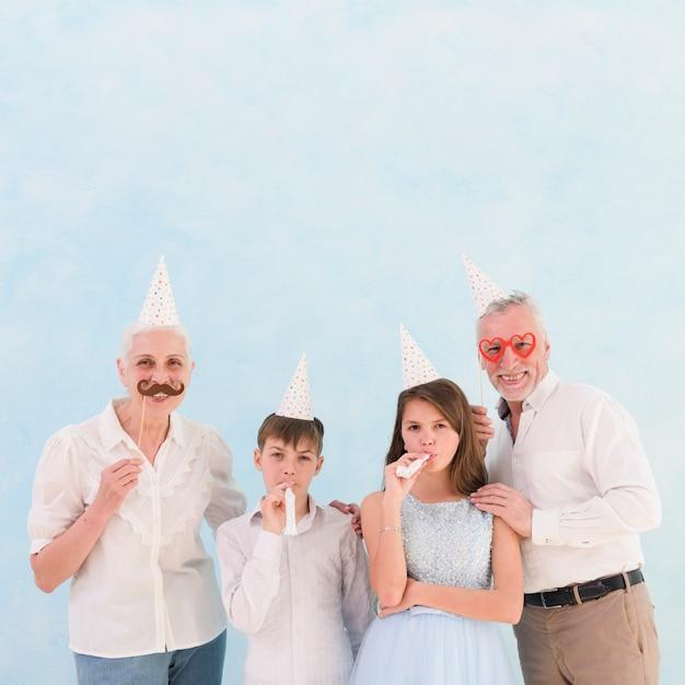 Kleinkinderen blazen feest hoorn met hun grootouders houden rekwisieten Gratis Foto