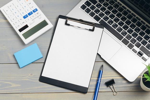 Klembord met blanco papier voor copyspace en benodigdheden op houten tafel Premium Foto