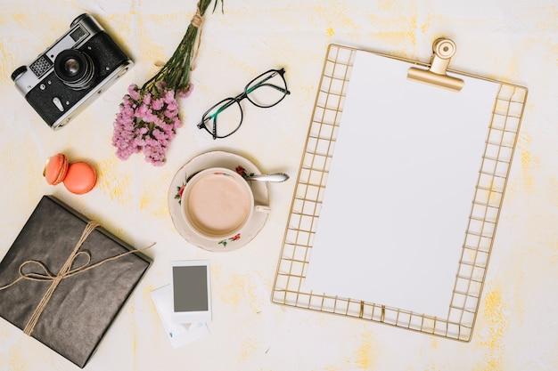 Klembord met koffie, camera en bloemenboeket op lijst Gratis Foto