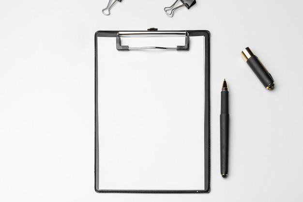 Klembord met wit blad en pen die op een wit wordt geïsoleerd. bovenaanzicht Premium Foto