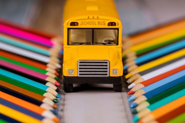 Kleurpotloden en gele schoolbus, terug naar school. Premium Foto