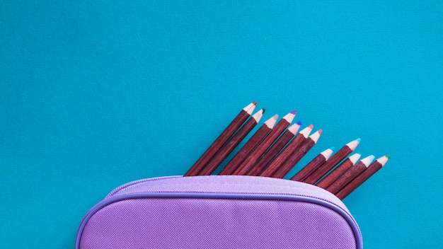 Kleurpotloden en paarse zak Gratis Foto