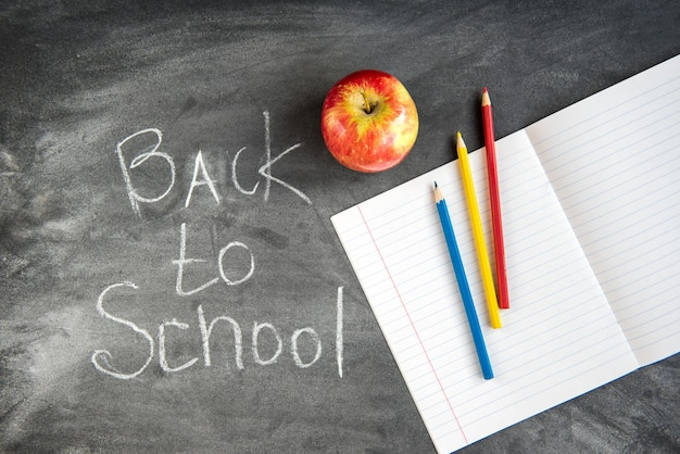 Kleurpotloden, voorbeeldenboek op zwarte bordachtergrond. terug naar school-concept. Premium Foto