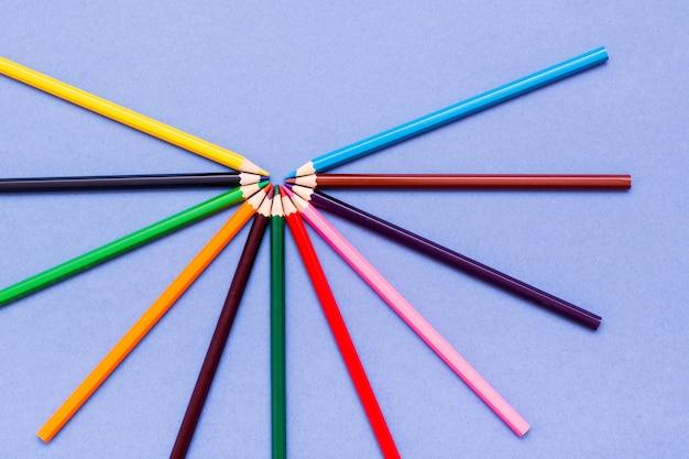 Kleurpotloden zijn uitgespreid op een blauwe bovenaanzicht Premium Foto