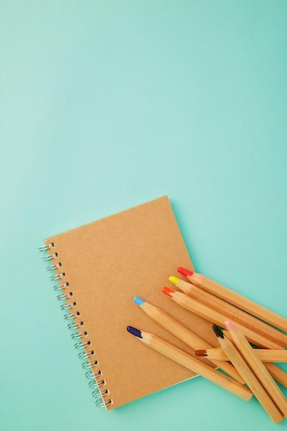 Kleurpotlood met een notitieboekje op blauw Premium Foto