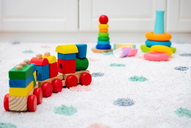 Kleurrijk babyspeelgoed op een tapijt Premium Foto