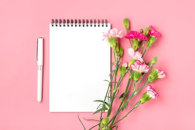 Kleurrijk boeket van verschillende roze anjerbloemen, wit notitieboekje, pen op roze achtergrond Premium Foto