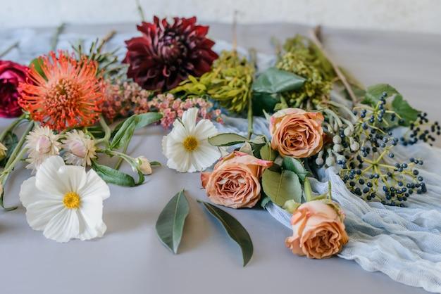 Kleurrijk boeket van zomer tuin bloemen. korenbloemen op oude armoedige tafel. vintage florale achtergrond. Premium Foto