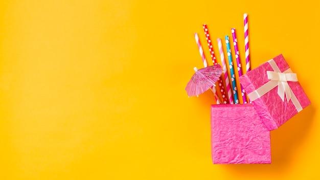 Kleurrijk het drinken stro met kleine paraplu in de roze doos op gele achtergrond Gratis Foto