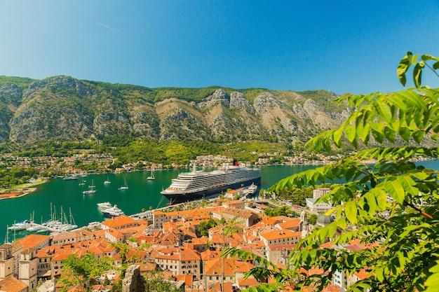 Kleurrijk landschap met boten en jachten in marina bay, zee, bergen, blauwe lucht. bovenaanzicht van de baai van kotor, montenegro Premium Foto